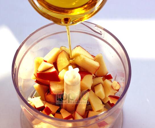 Cho táo đã thái nhỏ vào máy xay sinh tố, sau đó đổ thêm nửa bát dầu ôliu